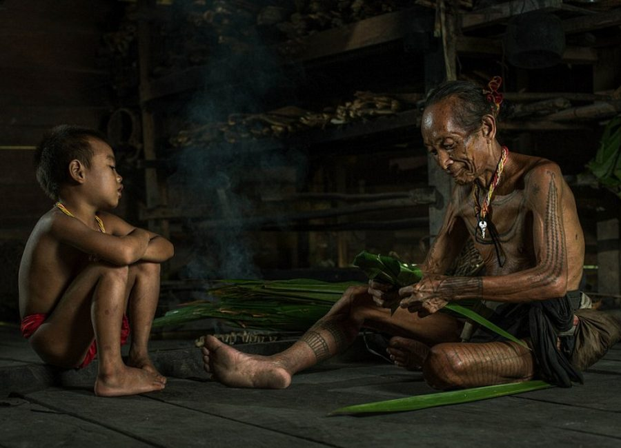 Generations-An-elderly-Mentawai-warrior-shows-a-young-boy-how-to-fold-what-appears-to-be-large-palm-or-banana-leaves