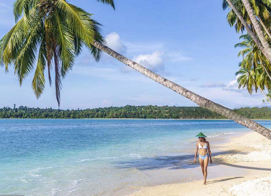 Indonesia, Sumatra, West Sumatra, Mentawai Islands, woman walking on the beach of a tropical island in the Indian Ocean